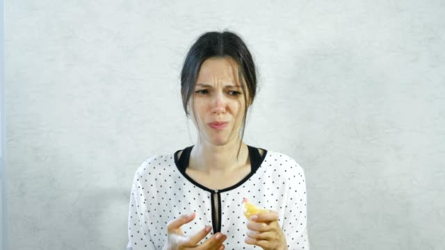 emotions from the sour on the girl's face. brunette woman eating sour tangerine and wincing. - gusto aspro video stock e b–roll