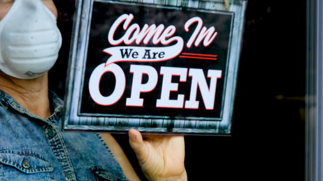employee changing the sign on closed business to open business - open sign stock videos & royalty-free footage