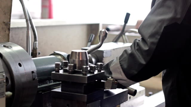 Employee drilling in flat steel plate with bench drill. video