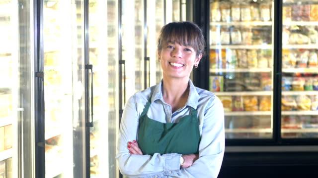 employee in frozen food section of grocery store - замороженные продукты стоковые видео и кадры b-roll