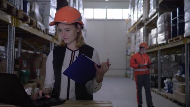 stockvideo's en b-roll-footage met medewerker dame in harde hoed gebruik laptop en maakt aantekeningen in kladblok op de achtergrond van magazijn medewerker - warehouse worker