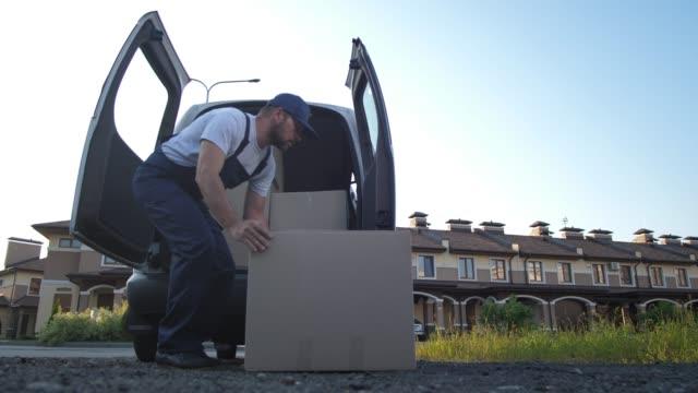employee of delivery service taking boxes from van - rozładowywać filmów i materiałów b-roll