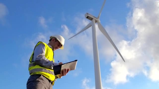 employee of wind power makes notes during the inspection of the mill - энергия ветра стоковые видео и кадры b-roll