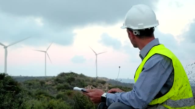 Employee of wind power makes notes during the inspection of the mill video