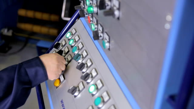 employee operates industrial panel with control buttons at a industrial plant - azionare video stock e b–roll