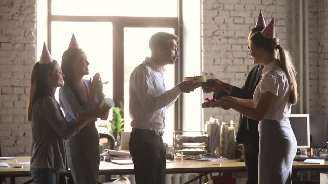 Employee receiving from colleagues birthday congrats during workday Man get from co-workers birthday cake blow candle feels gratitude, staff wearing party hats congratulating colleague presents a gift box clap hands cheering express respect and warm relation concept gratitude stock videos & royalty-free footage