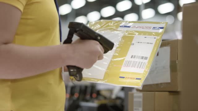 anställd som skannar stora kuvert för expresstjänster med en handhållen streckkodsläsare - kuvert bildbanksvideor och videomaterial från bakom kulisserna