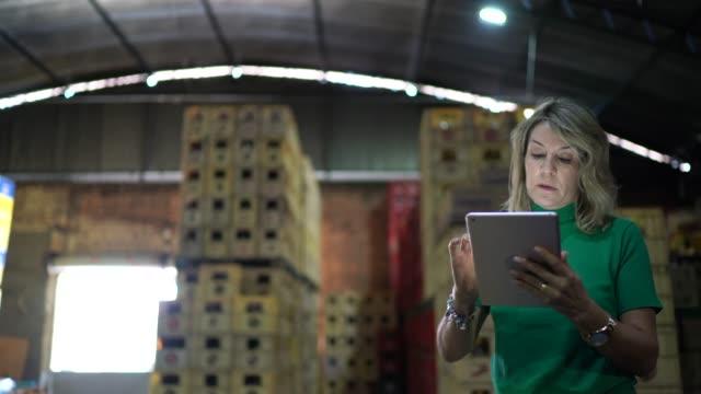 vidéos et rushes de employé marchant et utilisant la tablette numérique à l'entrepôt - inspecteur