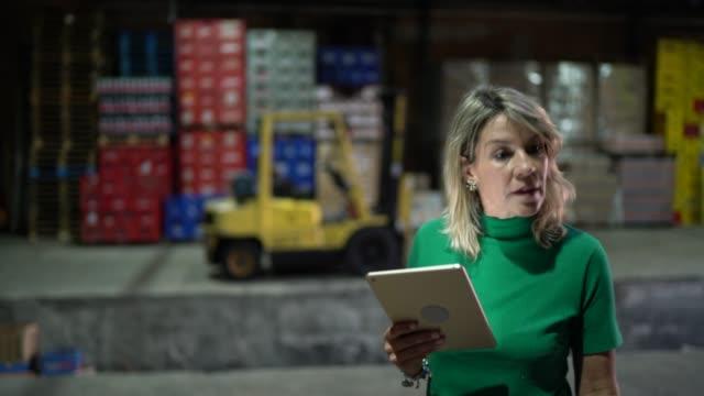 employee walking and using digital tablet at warehouse - prodotti supermercato video stock e b–roll