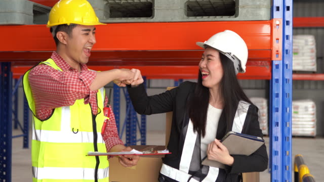 Employee woman and man in hard hat use digital teblet for checking inventory in warehouse store , success ,  hand greeting ,Fist Bump - vídeo