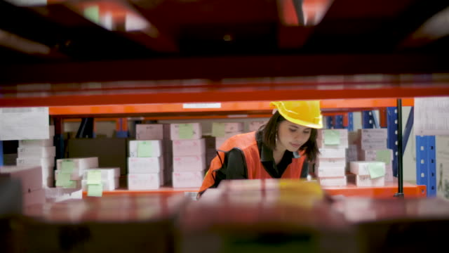 mitarbeiterfrau mit barcodeleser zur überprüfung des lagerprodukts in der lagerlogistik. - post it stock-videos und b-roll-filmmaterial