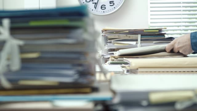 Employee working in the office and piles of paperwork