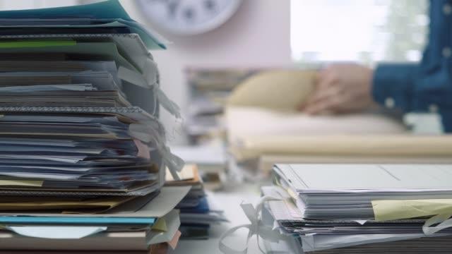 vídeos de stock e filmes b-roll de employee working in the office and piles of paperwork - dossier