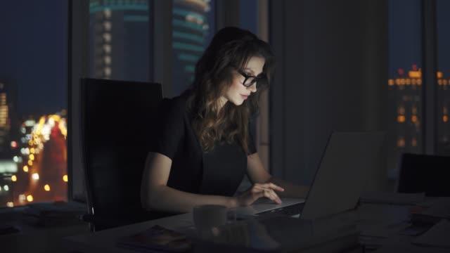 stockvideo's en b-roll-footage met werknemer werkt in het kantoor laat in de avond. meisje met een laptop op de achtergrond van de lichten van de nacht stad - portait background