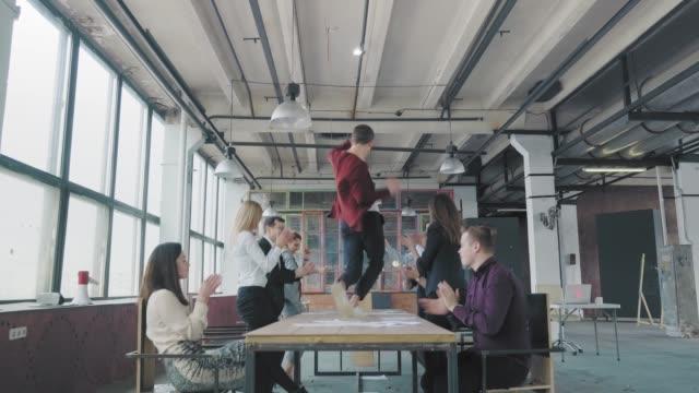 Mitarbeiter feiern das Ende des Projekts, haben Spaß am Tanzen auf dem Tisch. Seine Kollegen sprengen Flapper mit Konfetti in die Luft. Manager genießen Erfolg und Sieg. Corporate Party Business Team. Co-Working – Video