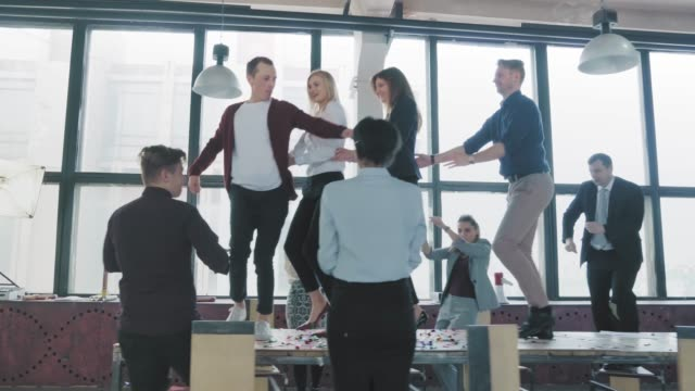 Employees celebrate the end of the project, have fun dancing on the table. Confetti fly around. Managers enjoy success and victory. Corporate party business team. Co-working video