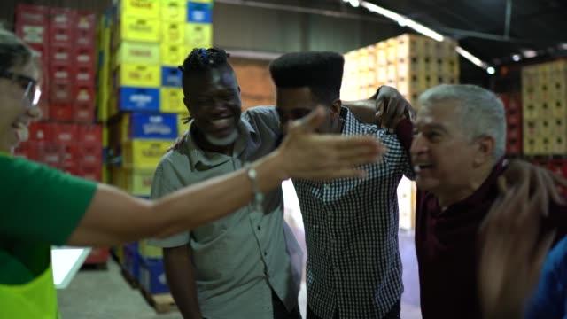 stockvideo's en b-roll-footage met medewerkers die goed nieuws vieren tijdens meeting on warehouse - huddle