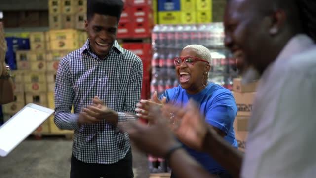 vidéos et rushes de employés célébrant de bonnes nouvelles à la réunion sur l'entrepôt - admiration