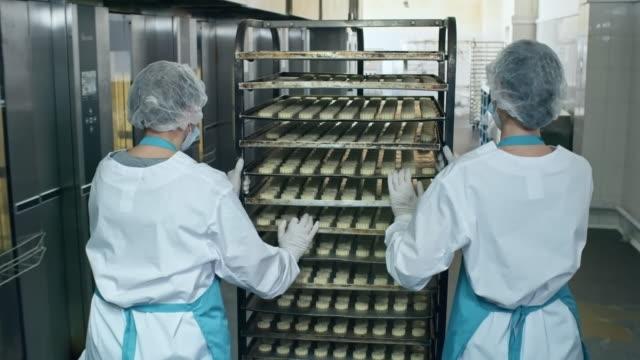 Employees Pushing Baking Rack at Factory