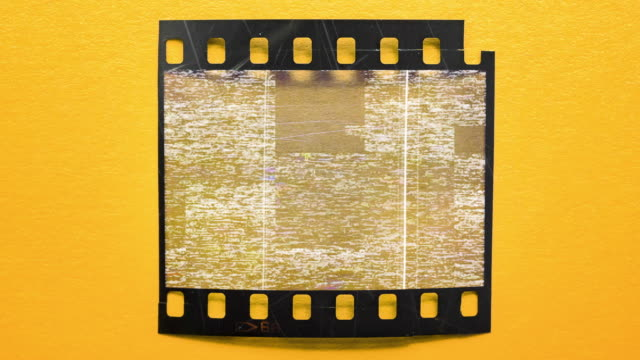 empty 35mm film strip with real VHS defects noise and artifacts, glitches from an old tape, black screen on 135 film material