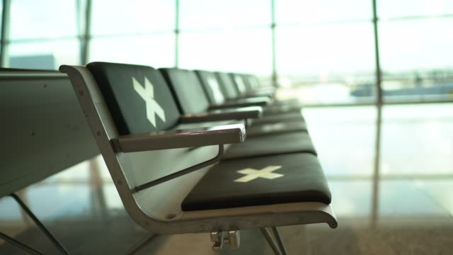 Empty airport waiting room with social distancing symbol on chairs