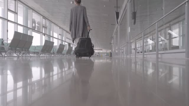 vídeos de stock e filmes b-roll de empty airport with tourist woman walking though the white hall with nobody. coronavirus covid 19 pandemic disease. delay plane and travel concept. tourism and holidays lifestyle in europe. - covid flight