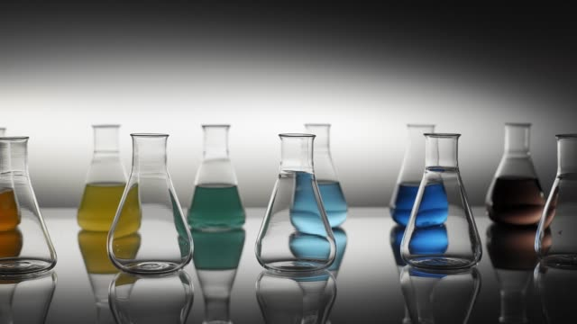 테이블에 반사 비어 있고 혼합 된 색상 액체 채워진 erlenmeyer 플라스크 - formula 1 스톡 비디오 및 b-롤 화면