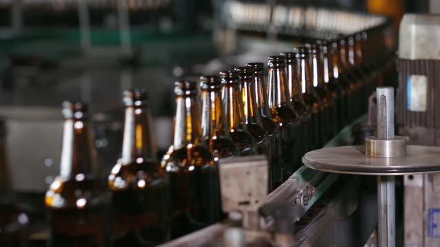 Empty beer glass bottles on the conveyor belt Technological line for bottling of beer in brewery. Empty brown bottles in a line in factory. Bottles Moving on Conveyor Belt at Glass Bottle Factory. Clean beer bottles are moving along the conveyor. bottle stock videos & royalty-free footage