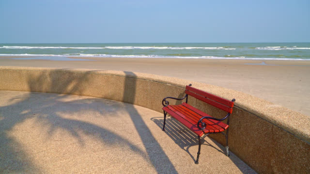 empty bench with sea beach and blue sky background - vídeo