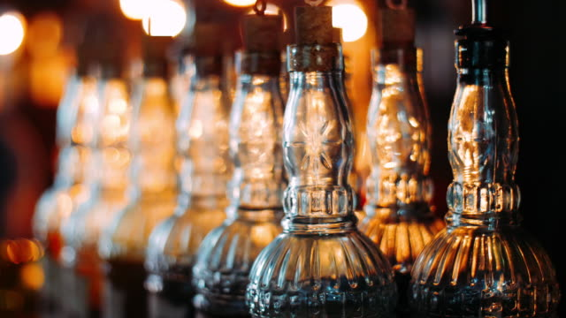 empty bottles with patterned glass are used when spilling alcoholic beverages - rum superalcolico video stock e b–roll