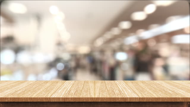 Empty brown wood table and blurred people shopping at supermarket light background. mock up backdrop template for product display.promotion stand.