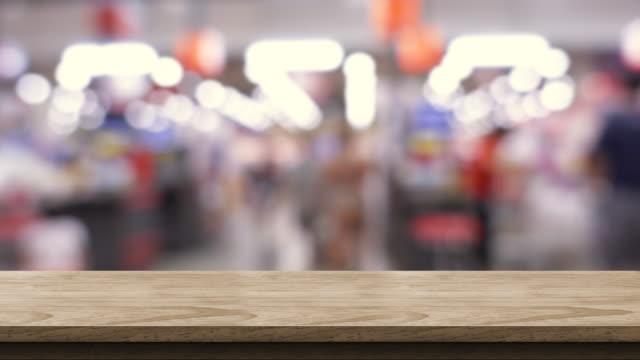 tom brun trä tabell suddiga människor shopping på stormarknad ljus bakgrund. håna bakgrund mall för produkt display.promotion monter. - dagligvaruhandel, hylla, bakgrund, blurred bildbanksvideor och videomaterial från bakom kulisserna