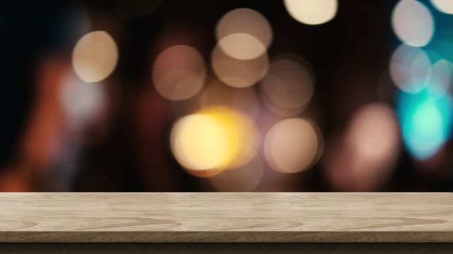 Empty brown wood table top with blur night club bar bokeh light background,Backdrop template for display of product or design,food stand mock up