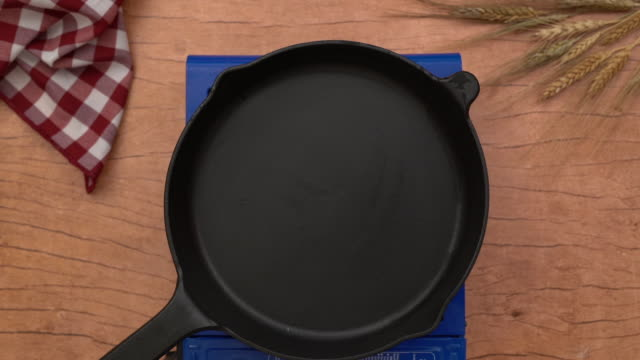Empty cast iron pan on burning gas stove on wooden background, top view, HD