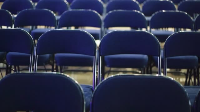 Empty chairs at a venue before a concert video