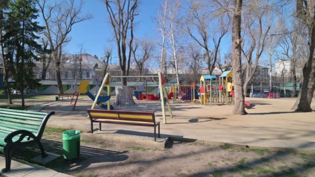 empty children playground in cathedral square park in the center of chisinau, moldova during state of emergency by the reason of covid-19 virus threat - молдавия стоковые видео и кадры b-roll