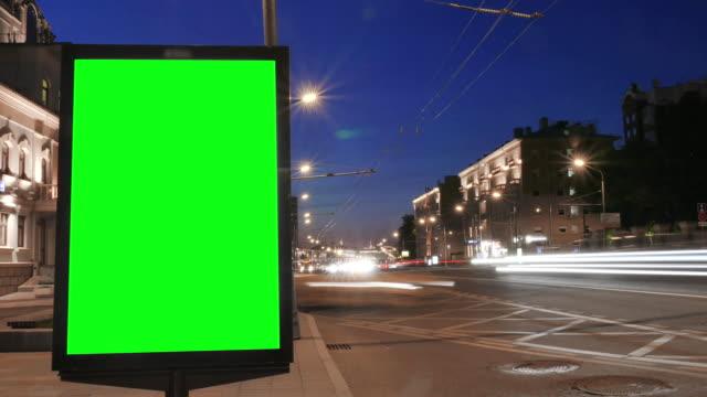 vídeos de stock, filmes e b-roll de a caixa vazia do citylight está pela estrada em edifícios timelapse - poster