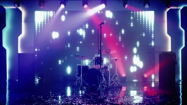 tom konsertscen i en nattklubb. professionellt trumset och annan musikutrustning för livespelning med rock band. konfetti på dansgolvet. ljusa färgglada strobing lampor på scenen. - trumset bildbanksvideor och videomaterial från bakom kulisserna
