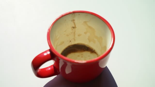 Empty cup of coffee. Dirty red cup Empty cup of coffee. The coffee is over. Dirty red cup. Dishes after the client. Fortune telling on the coffee grounds. Stains on the dishes. Cappuccino, cocoa, latte, hot chocolate. Morning mug stock videos & royalty-free footage