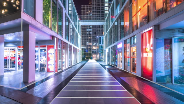 vídeos de stock e filmes b-roll de empty footpath between modern business buildings at night. time lapse - store