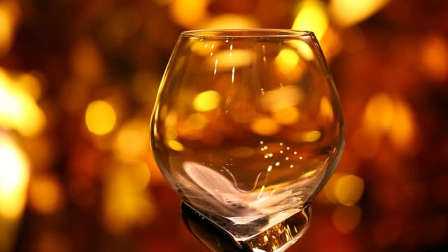 empty glass cognac gold bokeh hd footage - brandy video stock e b–roll