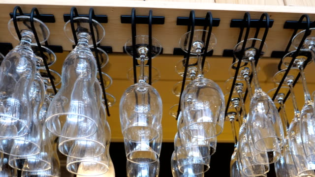 empty glasses hanging above the bar - bicchiere vuoto video stock e b–roll