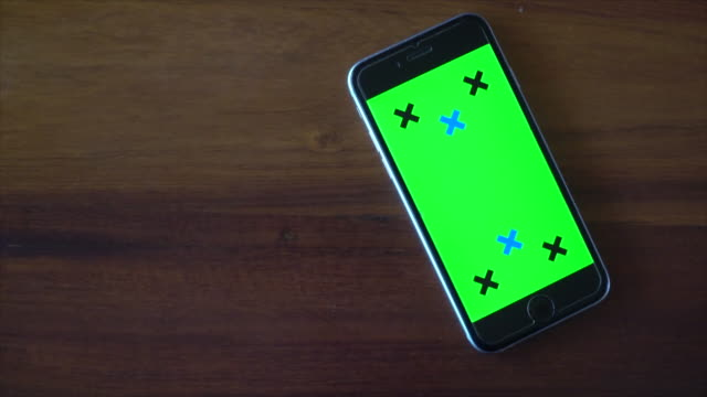 vídeos de stock e filmes b-roll de empty green screen phone on wood table - table