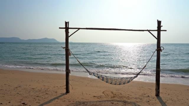 empty hammock on the beach and sea - amaca video stock e b–roll