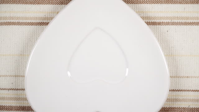 テーブルの上で回転する空のハート形の版 - ソーサー点の映像素材/bロール