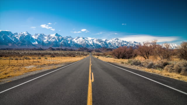 Empty highway in idyllic landscape with Sierre Nevada Mountains in the background, California A long, straight road stretches into the distance under a blue sky. Beautiful landscape with snowy mountains of the Sierra Nevada mountain range in the background. California, southwest USA. Camera panning down. western usa stock videos & royalty-free footage