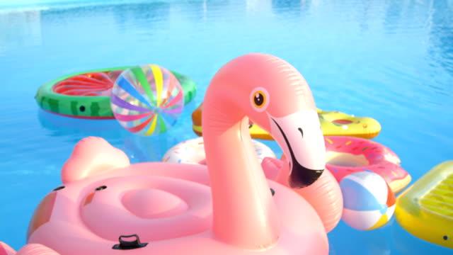 vídeos de stock, filmes e b-roll de inflável vazio flamingo, melancia, abacaxi e donuts flutua na piscina - flutuando na água