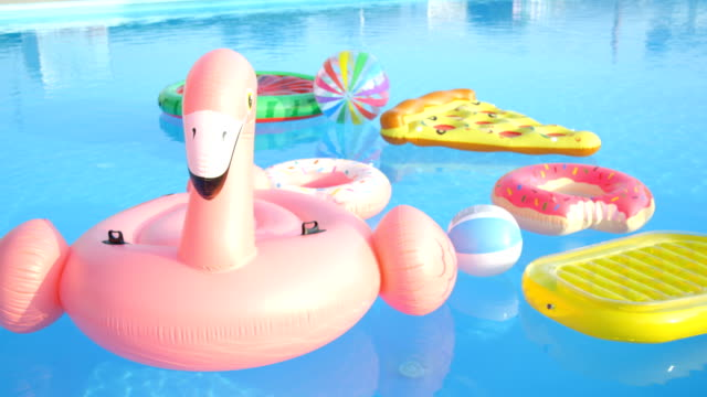 empty inflatable flamingo, doughnuts, pineapple and watermelon floats in pool - summer стоковые видео и кадры b-roll