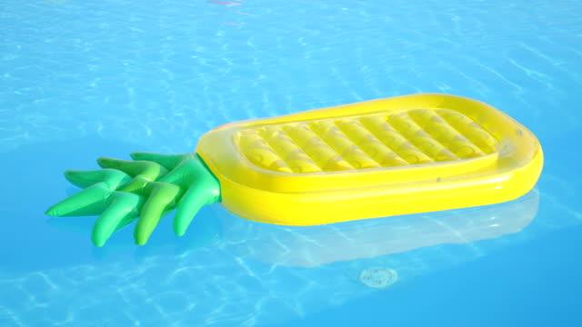 stockvideo's en b-roll-footage met close-up: lege opblaasbare ananas floatie drijven in het zwembad water - opblaasband