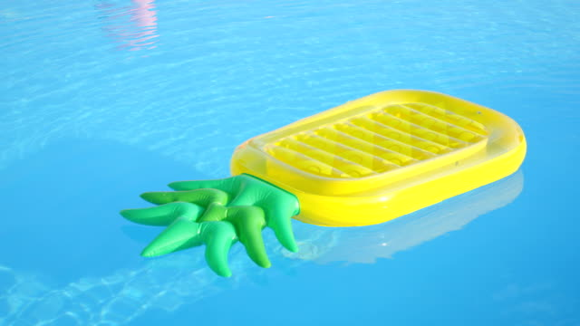 CLOSE UP: Empty inflatable pineapple floatie floating in pool water video